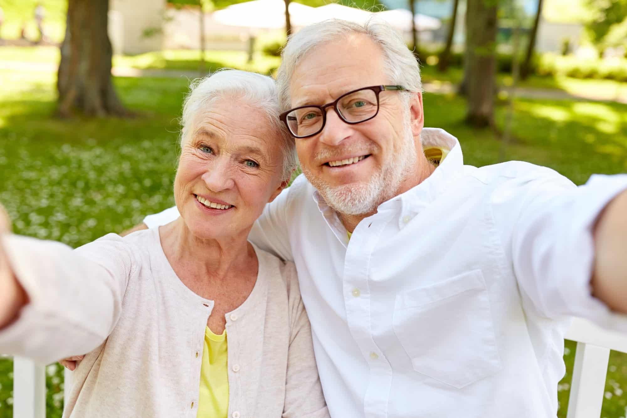 senior couple taking selfie at summer park