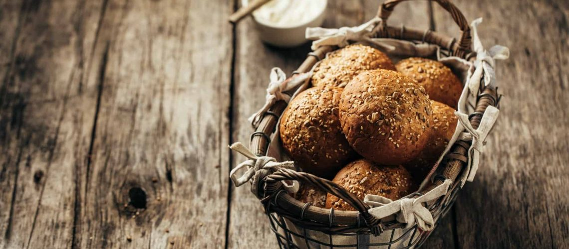 Whole grain bread rolls in a basket on a rustic wooden background.